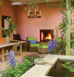 Peach-colored stucco wall in garden  with lime green porch furniture and plants~ love these colors.