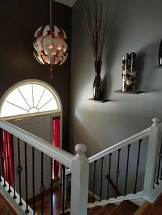 Split level house foyer can be made to be beautiful.  Floating  bracketless shelves with dramatic vases.