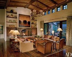 """In the living room, Saint Dizier installed """"a pastiche of furnishings invoking the wine countries of Italy, Portugal, Spain and France."""" Barry Masteller's Earth and Sky hangs above the fieldstone fireplace. Holly Hunt sofas, with Stark seat fabric."""
