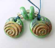 Round green earring dangles/charms are stamped with a swirl pattern…   http://artisancomponentmarketplace.com/metapolies/store/products/spiral-green-and-metallic-copper-earring-dangles-and-beads-pc14-101acm/   $10