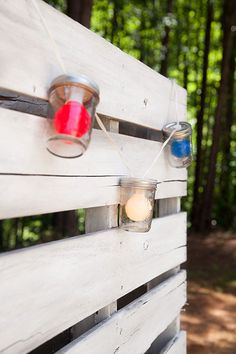 Fun July 4th and Memorial Day party lights idea: create diy mason jar lights by drilling a hole in the lids and securing red, white and blue string lights inside. Then hang your mason jar lights against a rustic white pallet!