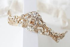 """Fit for royalty, this couture handcrafted Gold crystal Bridal tiara crown is created using antique gold plated stampings soldered together so it lasts you a life time and then set each and every crystal by hand.- Handcrafted withPremium European crystals- Each stone is set by hand in my studio- Golden shadow, clear and white opal stones- Antique gold finish- Headpiece measures 17 inches and is 2"""" tall in the center. Has loops at ends to secure with bobby pins.- Handcrafted in the ..."""