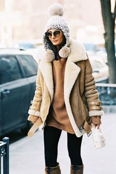 Giovanna Battaglia wears a camel sweater, shearling-lined moto jacket, leggings, fur knee-high boots, and playful accessories