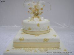 Ivory two tier stacked 50th golden wedding anniversary celebration cake with gold sugar 50s and hearts trimmed with gold chiffon ribbon. Topped with an explosive feathered gold heart and starburst topper