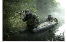 Navy SEALs navigate the waters in a folding kayak during jungle warfare…
