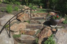 stone steps and boulder retaining wall with metal handrail