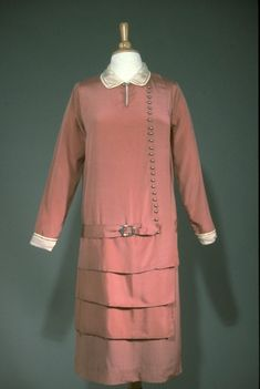 Dress, 1926, of rose pink rayon and silk, with ivory silk Peter Pan collar and with cut-out stitched trim. 24 silver ball buttons on left side, & geometric triple-tiered ruffles with drop-waist & self-fabric belt with silver buckle. Long, straight sleeves with ivory satin cuffs with stitched trim; single snap closure.