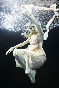 Posing underwater is one of the hardest types of modeling. Creamy skin, blonde, flowing dress.