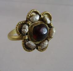 A remarkably rare Ottonian gold ring with pearls, and a cabochon garnet.