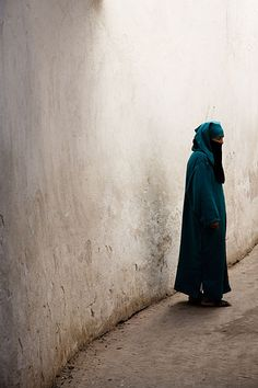 Woman walking in one of the many narrow alleys in the Fes Medina