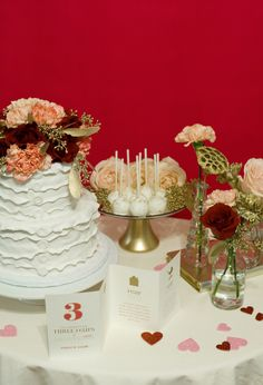 white ruffle cake and flower topper by http://www.100layercake.com/blog