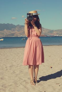 Her pink dress fell neatly around her knees, billowing slightly, just the way she liked it. With the warm sand beneath her toes and the salty wind in her air, she wanted to live in the moment forever. But she settled for the next best thing: a photograph.
