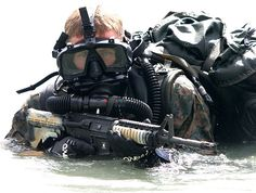 A Force Recon Marine with II MEF Force Recon Company, rises out of the surf. The Marine is wearing a closed-circuit rebreather system which allows the wearer to breath submerged down to a depth of 50 feet. Note the large waterproof ruck sack strapped to the Marine's back. Force Reconnaissance Marines may need to carry enough gear to sustain them for up to 6 days or more.