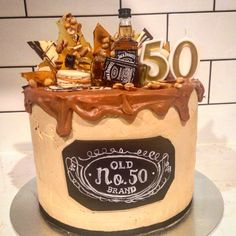 Jack Daniels 50th birthday cake. Layers of chocolate cake, Victoria sponge, hazelnut meringue, salted peanut caramel, chocolate smbc, choc chip smbc. Iced in salted caramel smbc with caramel drip. Topped with chocolate shards, nut toffe shards, macarons & mini bottles of jack. Old no. plaque hand drawn.
