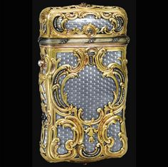 A Fabergé jeweled gold and enamel cigarette case, workmaster Michael Perchin, St Petersburg, circa 1890. Of upright shaped rectangular form, the surface enameled in translucent pearl grey over chevron engine-turning, overlaid with gold cagework chased with leafy scrolls and set with rose-cut diamonds.