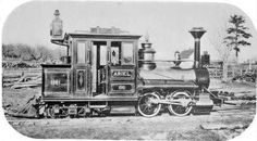 """""""Ariel"""" was one of two diminutive steam engines built by Hinkley Locomotive Works of Boston for the Billerica & Bedford Railroad, Massachusetts. In this rare 1877 photograph, Ariel is seen at the Bedford end of the line. In the distance (to the left of the smokestack) the B's Car Shed is visible."""