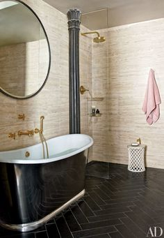 The master bath of John Legend and Chrissy Teigan's home features travertine walls and a black limestone herringbone floor.