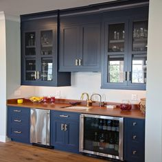 Navy blue kitchen wet bar, fitted with shaker cabinets painted Benjamin Moore Hale Navy and accented with brass pulls, features wood countertops holding a sink with a brass gooseneck faucet flanked underneath by a stainless steel mini fridge and a glass front wine fridge while above glass front china cabinets flank slight smaller close cabinet doors.