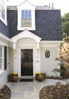 Pediment door hood with corbels / brackets. Black front door. Gambrel style roof.