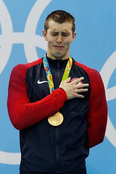Gold medalist Ryan Held of the United States shows his emotion on the podium…