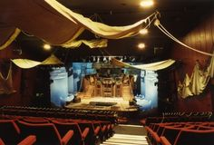 Colour photograph showing the stage at the Gateway Theatre in Chester. Taken from an aisle on the stage left side of the auditorium, high up on the steeply raked seating, it shows the stage, proscenium and ceiling. There is scenery on stage depicting the deck of a boat at sea, and the auditorium has been similarly decorated; sails hang from the ceiling and sidewalls.