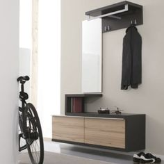 I like this modern style hallway cabinet. We can see vertical, horizontal lines. There is rectangle shape on front of drawer. There is mirror also .mirror can make area big. Colours are light and dark for furniture, wall is painted in neutral color. We can see big window source of natural lighting.
