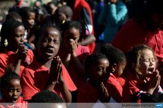 SOUTH AFRICA, Pretoria: Children pray in front of the Medi Clinic Heart hospital in Pretoria on June 27, 2013. South African President Jacob Zuma said today that the condition of ailing anti-apartheid hero Nelson Mandela had improved overnight and was now critical but stable. AFP PHOTO / Filippo MONTEFORTE