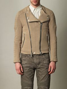 Beige jersey collarless jacket with quilted shoulder and elbow patches and zipped cuffs. With a lightly distressed, worn appearance, the jersey jacket from Balmain offers a relaxed take on the classic biker look - a true rock 'n' roll investment piece.