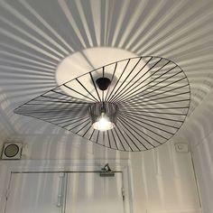"""Suspension de """"petit"""" format dans la collection Vertigo, composée d'une rosace de plafond blanche et d'un cordon d'alimentation gainé de tissu blanc supportant une structure ronde constituée d'arceaux en fibre de verre agrémentés de rubans de polyuréthane, Vertigo est présentée ici dans une finition de coloris noir. Graphique et aérienne, cette création poétique incontournable a été imaginée par Constance Guisset,"""