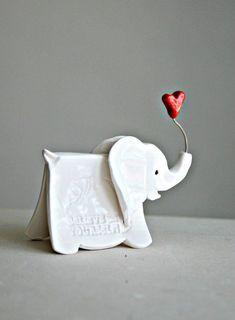Petit éléphant sculpture avec des mots imprimés de sagesse et tenant un coeur dans son coffre.: