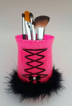 Glass Make up holder. (Makeup brushes not included) Corset and bow made with black vinyl. Clear rhinestones on each end of corset ribbon and silver rhinestone in middle of bow. Black feather trim around bottom of cup. Hot pink chunky glitter inside cup has been sealed so it wont