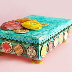 Decorate a purchased wooden box using ink, paper circles, and fabric flowers for an artsy jewelry box. Button stacks form fun legs./