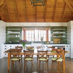Green backsplash and chair cushions help with this kitchen's natural look. | Coastalliving.com