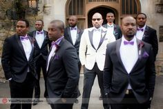 Polished groomsmen in their black tuxes with a hint of violet peeking out from their boutineer and bow tie, a perfect choice for a perfect occasion.