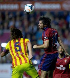 Alejandro Arribas Garrido (R) of CA Osasuna wins the header before Carles Puyol of FC Barcelona during the La Liga match between CA Osasuna and FC Barcelona at El Sadar stadium on October 19, 2013 in Pamplona, Spain.