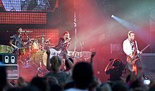 Muse-- are an English rock band from Teignmouth, Devon, formed in 1994. The band consists of Matt Bellamy (lead vocals, guitar, piano, keyboards), Chris Wolstenholme (bass guitar, backing vocals) and Dominic Howard (drums, percussion).