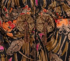 SILK and GOLD LAME EVENING COAT, c. 1920. Black silk having pink, gold and orange floral print with metallic gold brocade floral, ruched along top of sleeve, neckline trimmed in gold cord, hook & eye closure beneath pair of metallic roundels with beaded tassels, lined in pale yellow satin. B-44, L-49. (Roundels and lining possibly replaced) excellent. $1,560.