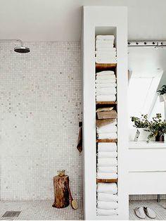 El espacio dedicado a la ducha, divídelo en dos dejando menor espacio para el baño y creando un lugar de almacenaje extra que te ayudará de forma súper práctica para guardar toallas y accesorios.