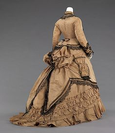 Tan silk walking dress with black lace trim (back), American, 1870-75. This is a nice example of an early 1870s bustle day dress worn for promenading and visiting.