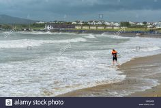 Download this stock image: Body boarder enters the sea on a stormy day at…