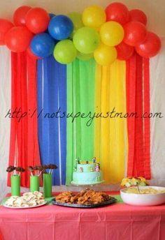 Mesa de postre decorada con globos y papel crepe