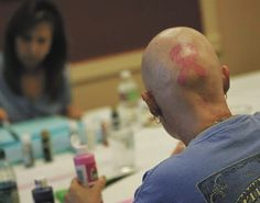 Etched on the back of Suzette Collins' bald head is a pink ribbon, the symbol for breast cancer awareness.