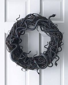Materials • Black acrylic paint  • Vinyl snakes from $1 store  • Floral wire, 20-gauge • Black water-based spray paint • 18-inch grapevine wreath Paint grapevine wreath using water-based spray paint; let dry. Paint vinyl snakes in assorted shapes and sizes using acrylic paint; let dry. Attach snakes to wreath: For flat snakes, twist floral wire around in two places, thread wire into wreath, and secure at back. Coiled snakes can simply be wrapped around wreath.