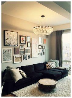 decoração sala: Sofá preto e parede de quadros.