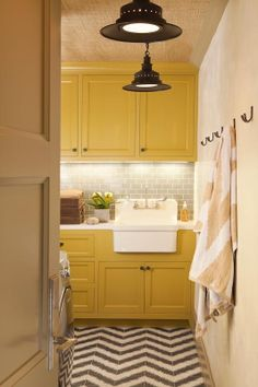 Beautiful yellow cabinets in laundry room. & I love the stenciled floor!!