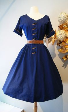 This is a fun 1950s dark blue/navy cotton day dress! The touch of brown piping is a nice little accent of color! The cuffs are folded up and are