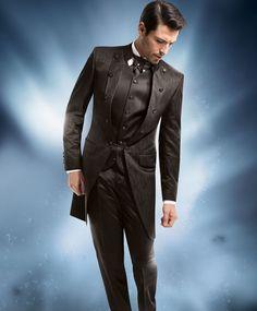Moccafarbener Royal-Gehrock in einem exklusiven Fantasiejacquard mit extravagantem Borkendessin sowie unifarbener Weste und Hose. Der Plastron mit Einstecktuch ergänzen das Outfit.