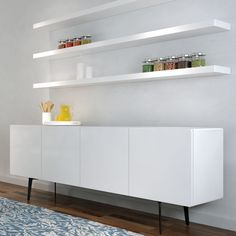 Clean White Floating Shelves above Long White Cabinets Placed in Simple Room with Laminate Oak Flooring