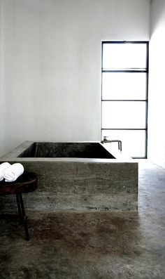 concrete bathtub, white walls