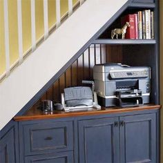 under-stair storage ftw: An under-the-staircase space provides storage for a shared printer and hole punch. The grown-up decor echoes the one upstairs.